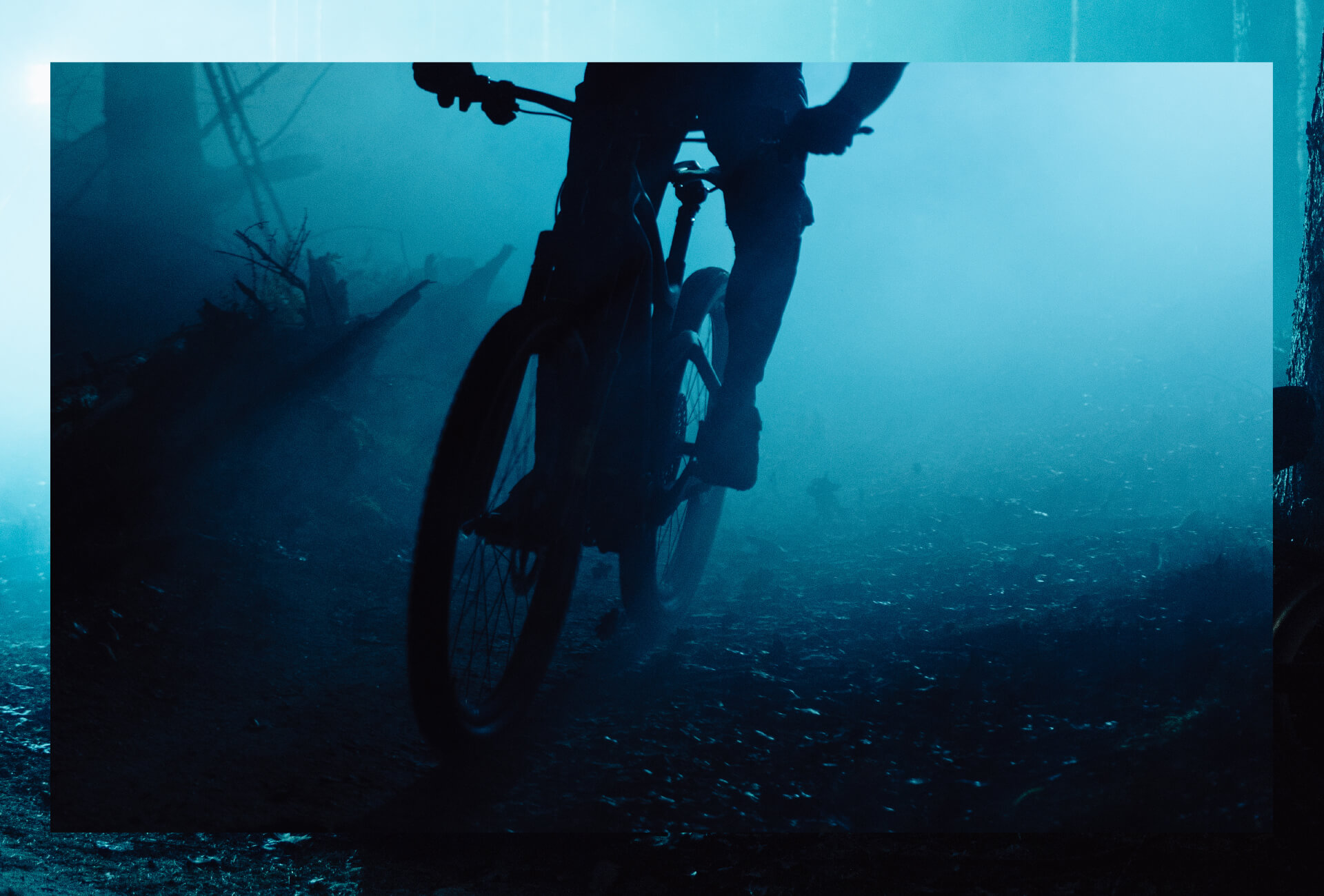 Someone riding a mountain bike through a dark forest with blue lights in the background