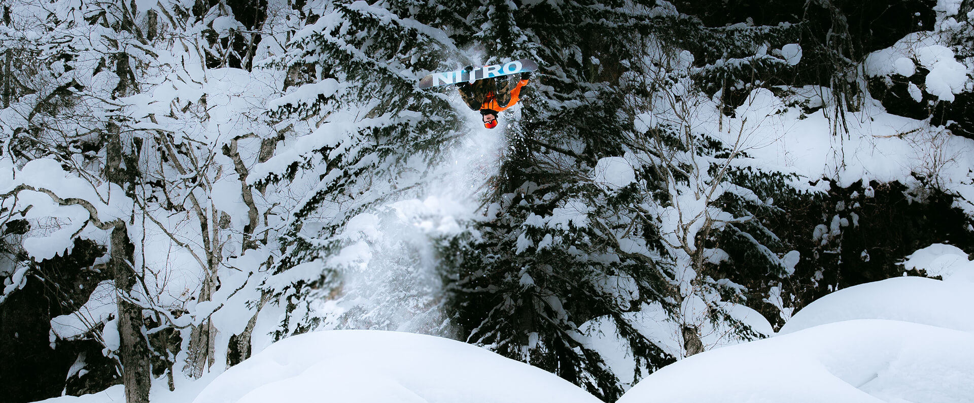 Haibike Hero Victor Delerue doing a backflip on his snowboard in a snowy forest