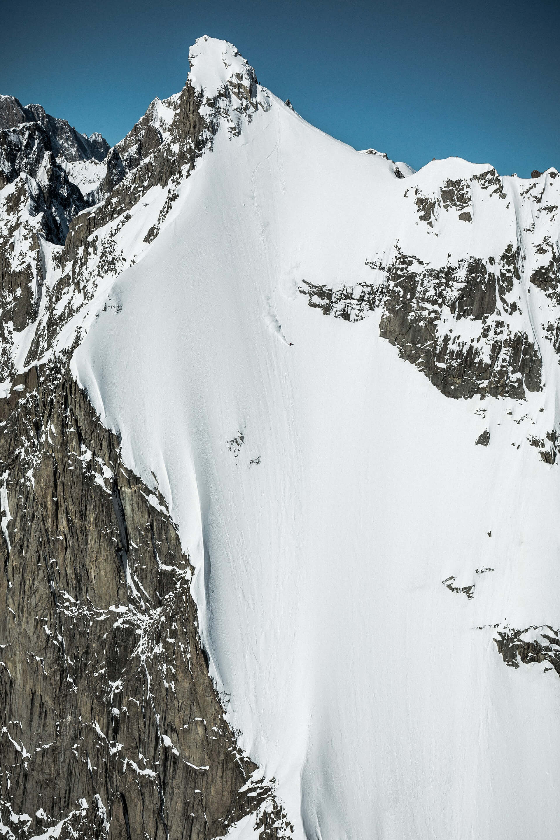 Wide angle shot of Haibike Hero Victor Delerue standing on top of a high mountain waiting to descend with his snowboard
