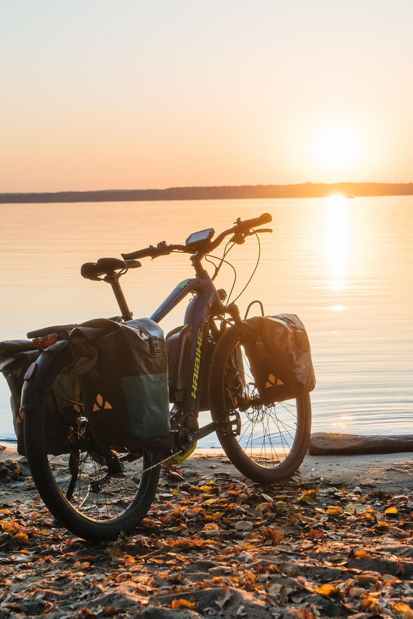 Trekking bike in front of a lake with sunset