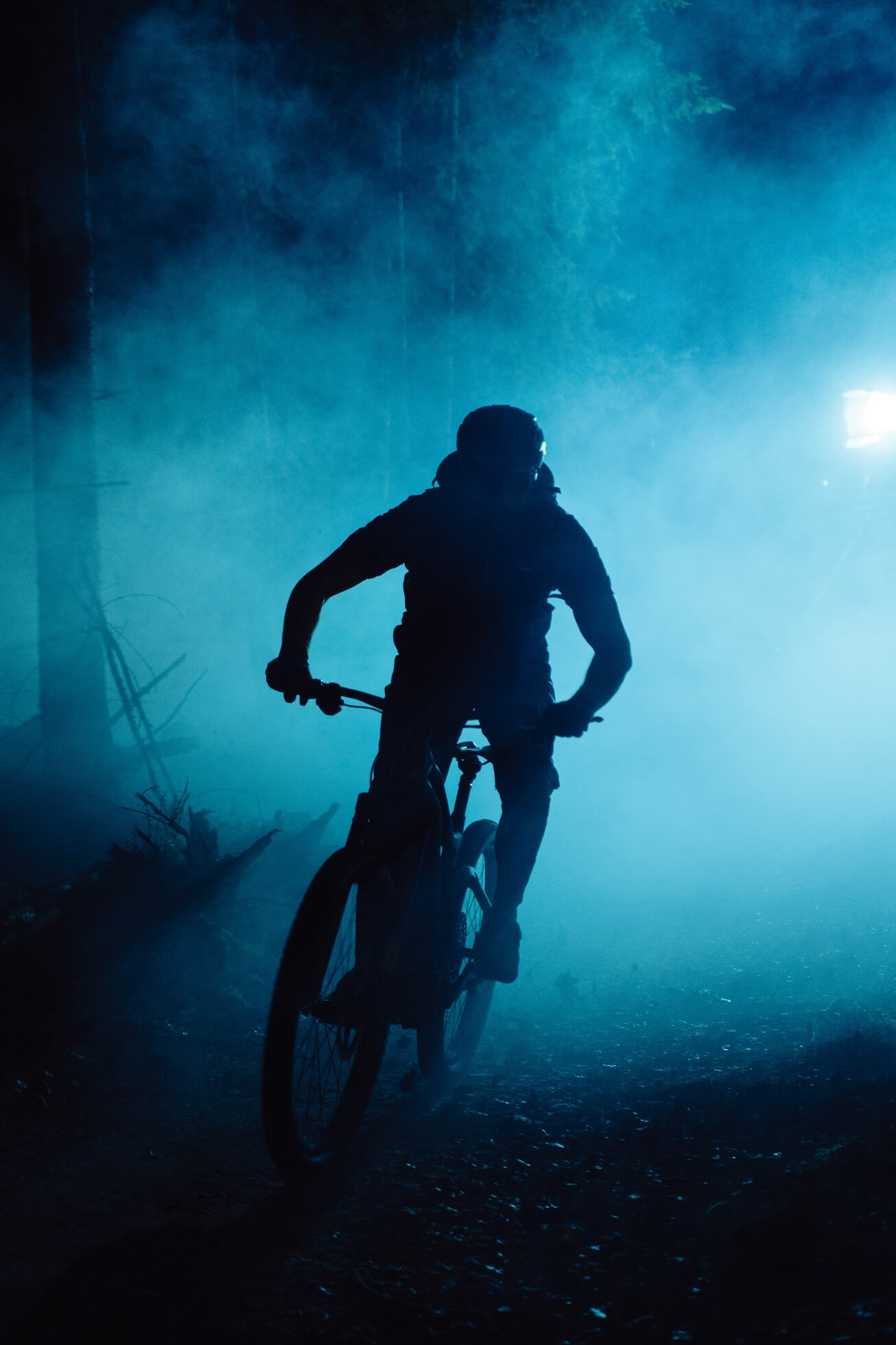Silhouette of a man riding his mountain bike in a dark forest with blue lights in the background